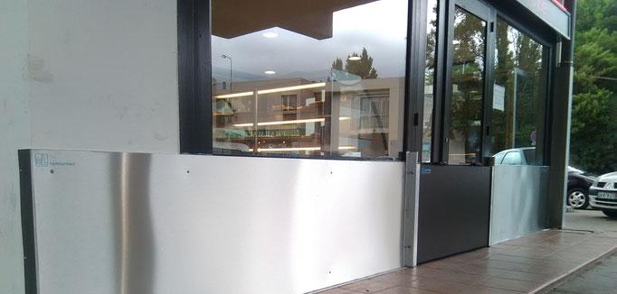 Batardeaux anti inondations Montpellier, barrière centrale avec panneau amovible, vitrines situées de part et d'autre de l'entrée équipées de barrières anti inondation fixes