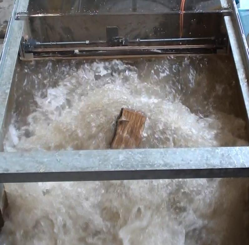 Bac d'expérimentation CERISIC avec un lâcher d'eau avec vagues et des rondins sur le modèle pour tester la résistance du batardeau. Test résistance réussi!