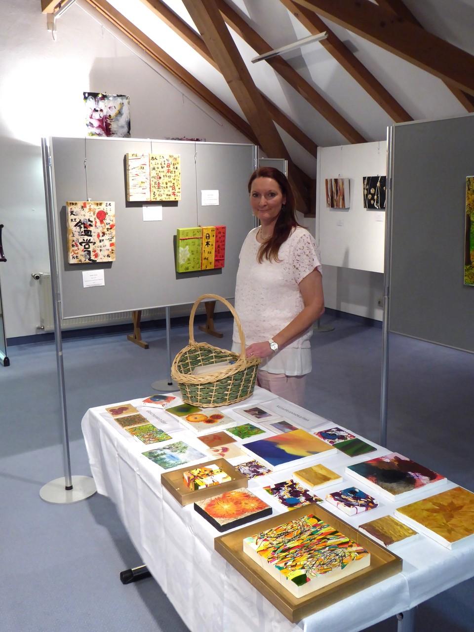 Der Tisch mit dem Postkartenkörbchen und den Geschenkebildern