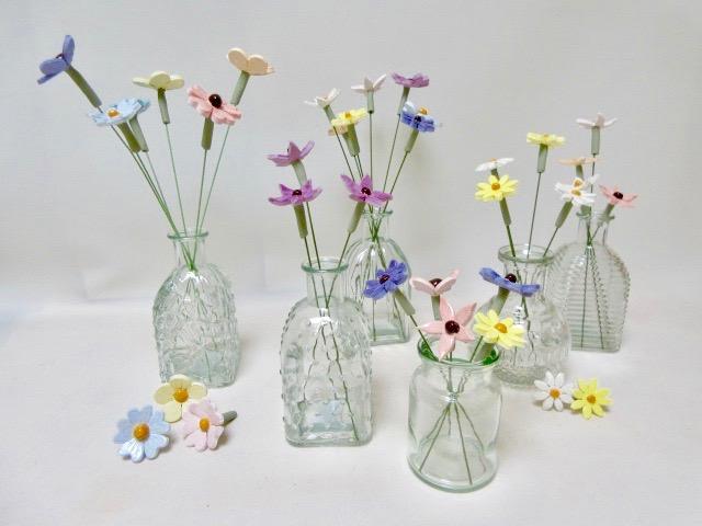 Allerlei kleine bloempjes in glazen vaasjes