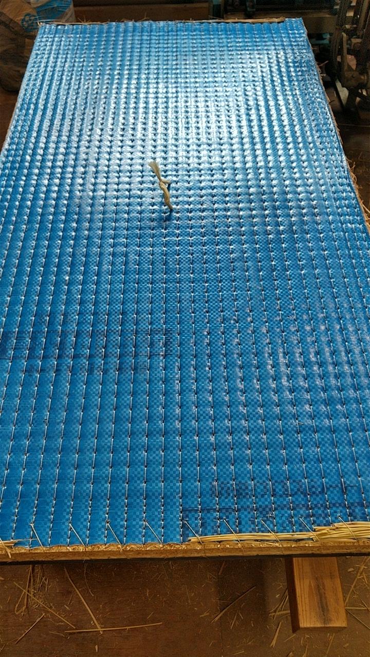 本床裏側(藁床)、手縫いしたコーナー(補強材)の糸を足で締め込みました。