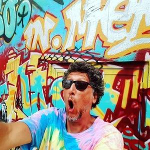 Guillaume Chérel fait le pitre dans une cité devant un mur de tags