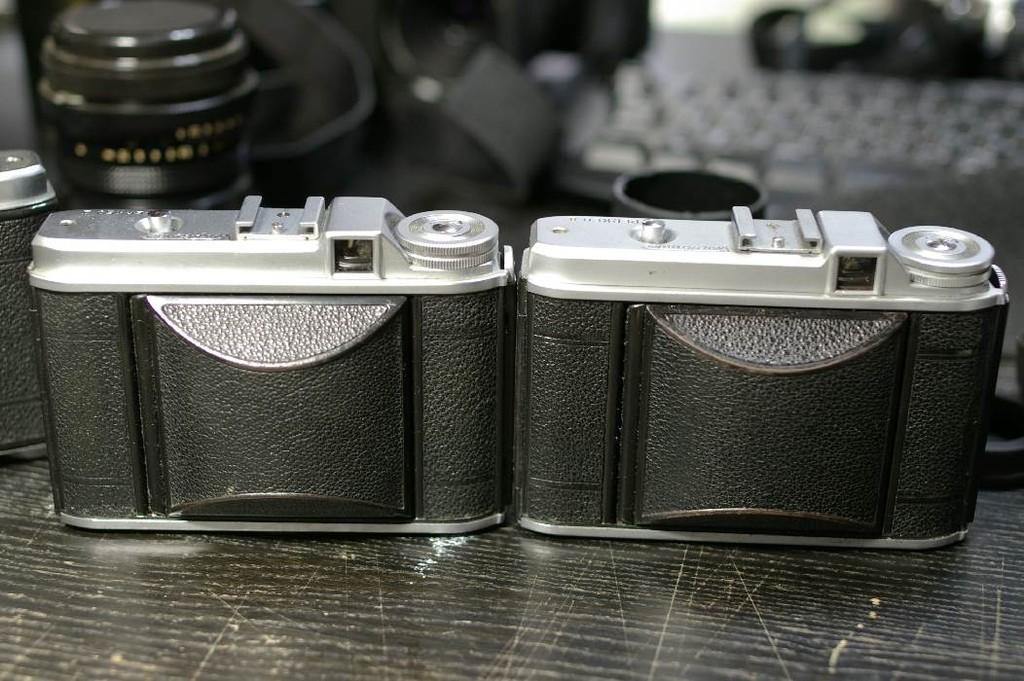 右は前期型、左が後期型。前期型の方が2mm薄い。レンズ格納蓋の形状が違う。