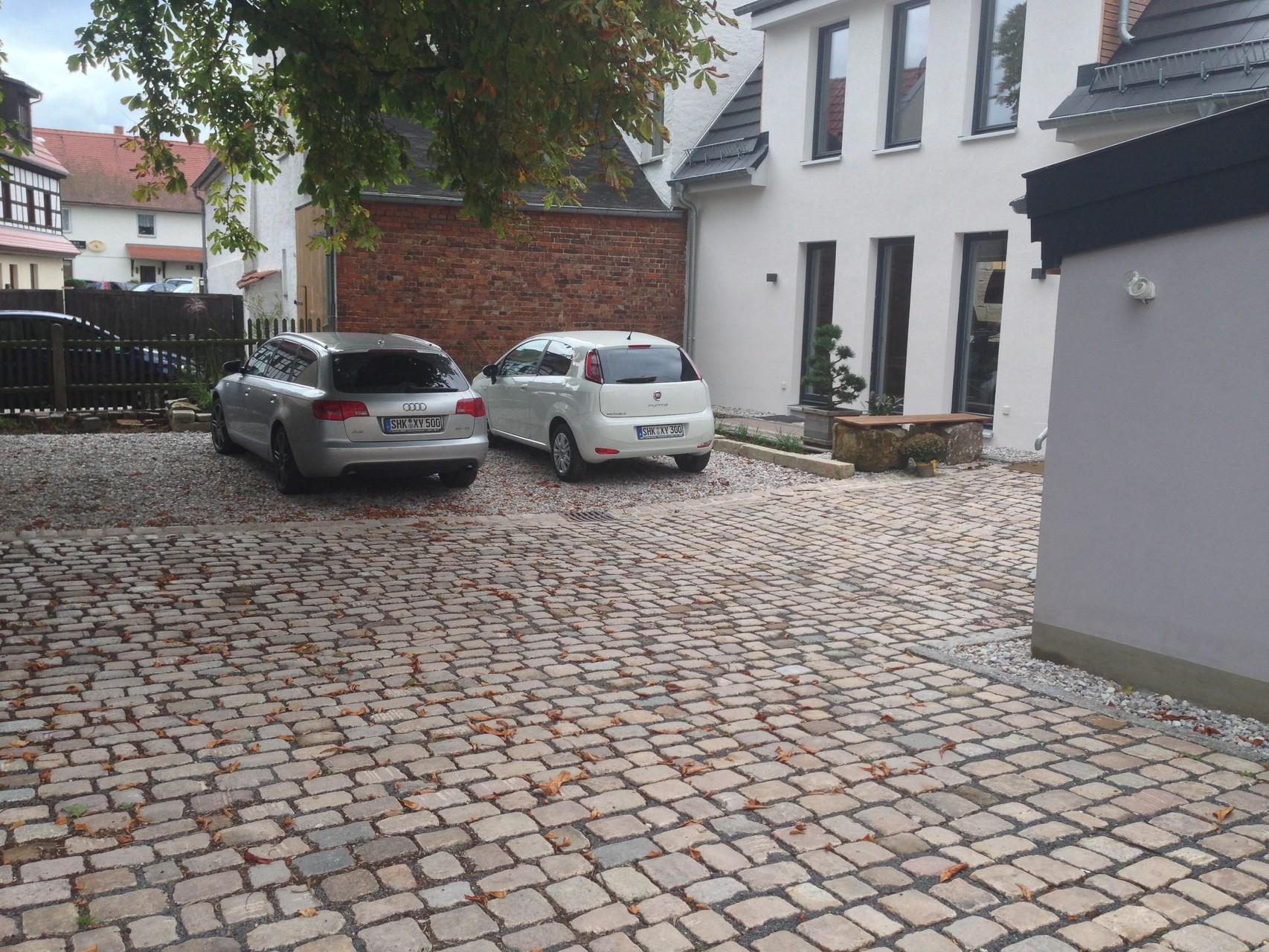 Hinterhofgestaltung mit Naturstein-Großpflaster und Rollkies
