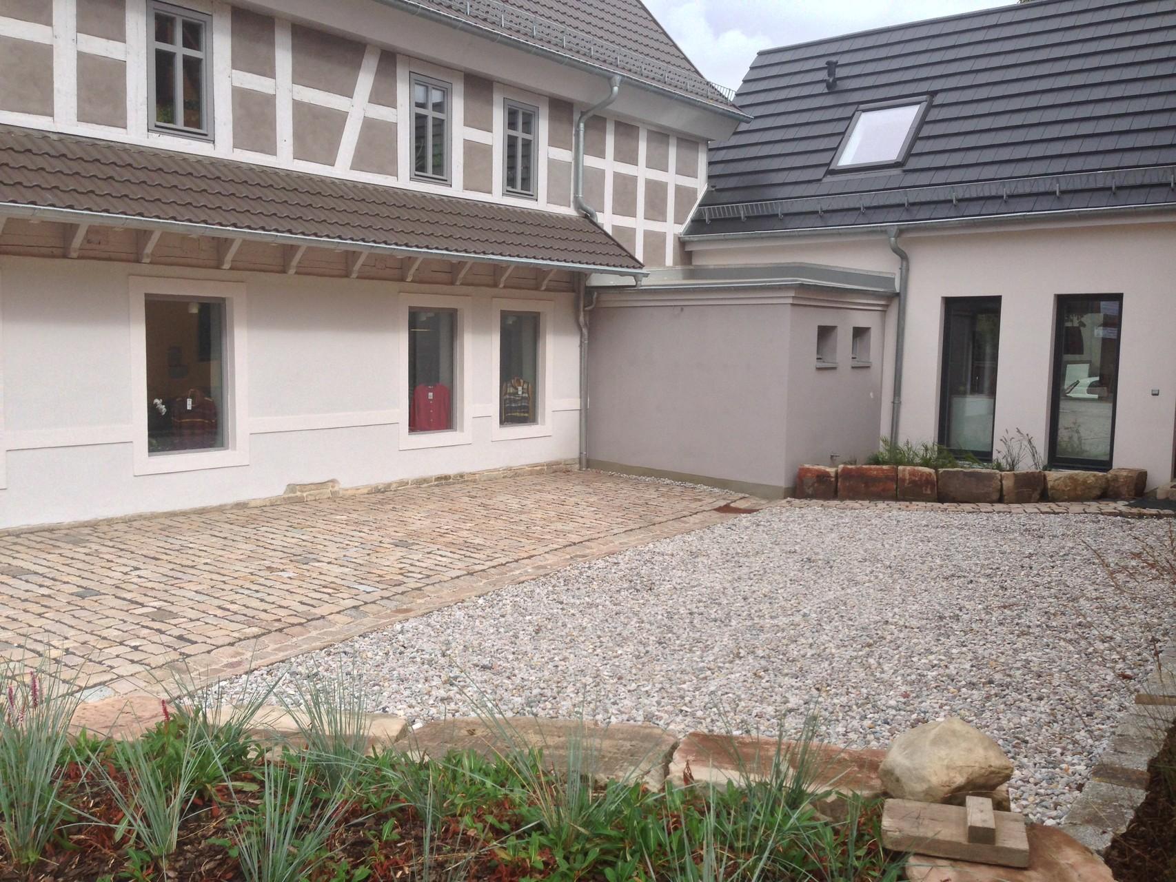 Vorderhofgestaltung mit Naturstein-Großpflaster und Rollkies
