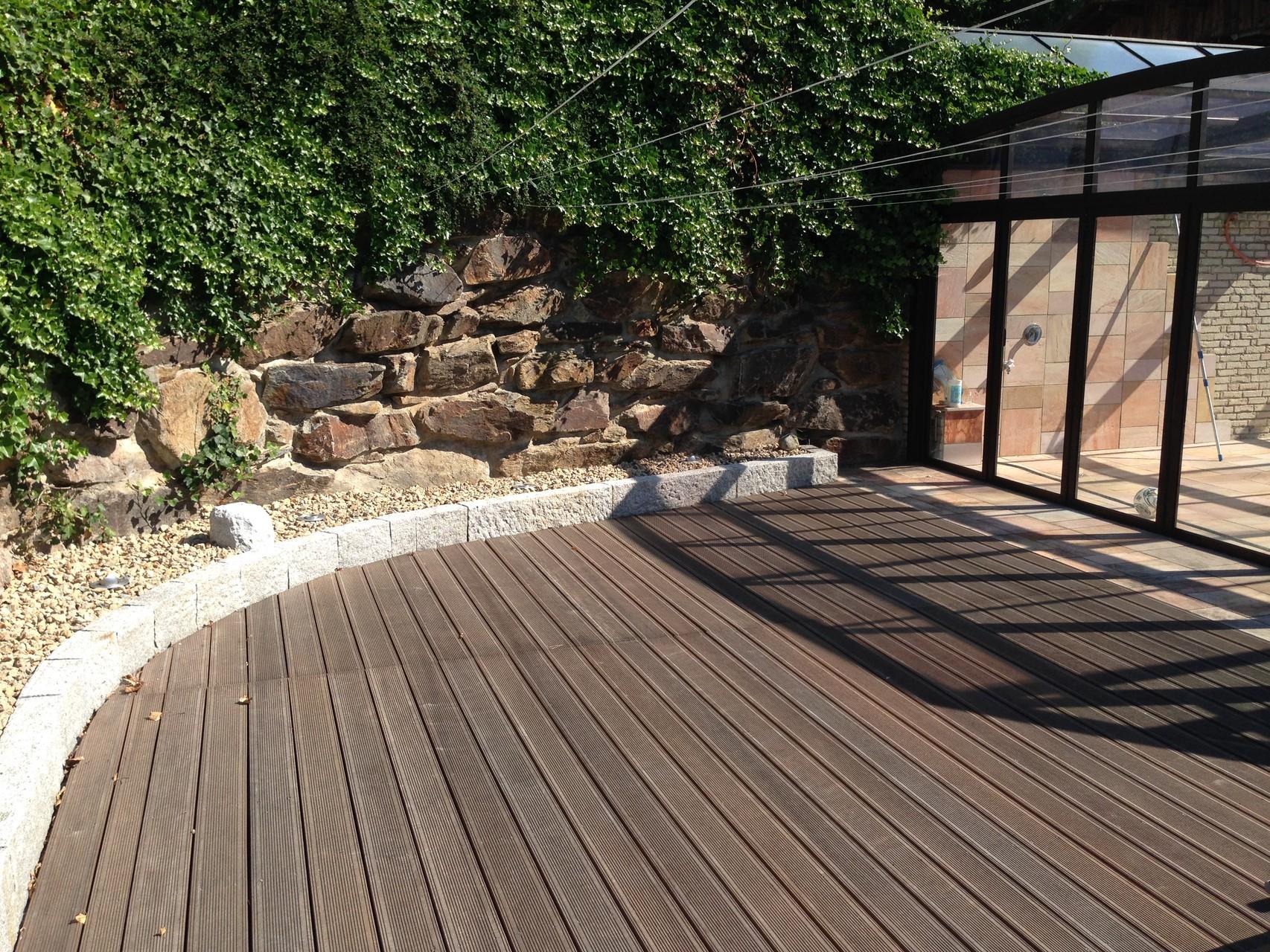 Terrassengestaltung mit Holzbelag und Natursteineinfassungen
