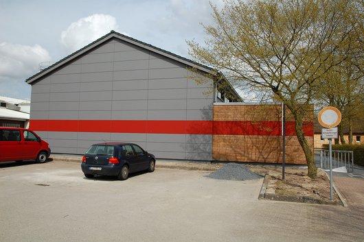 Der Eingang zur Turnhalle liegt rechts neben dem Gebäude und ist über einen Fußweg erreichbar.
