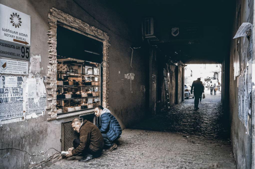 """Двое мужчин возятся с электрическим удлинителем в тбилисском пассаже. В этой сцене фотограф Вахо Долидзе увидел аллегорию сегодняшнего положения вещей в стране: """"Мы, грузины, в темном туннеле. Он скользкий и коварный, но мы видим свет в дали. Мы знаем, чт"""