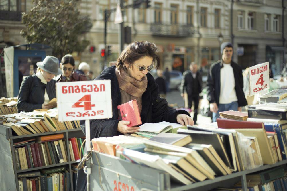 Девушка рассматривает подержанные книги в центре Тбилиси. Фото: Indigo Fleur