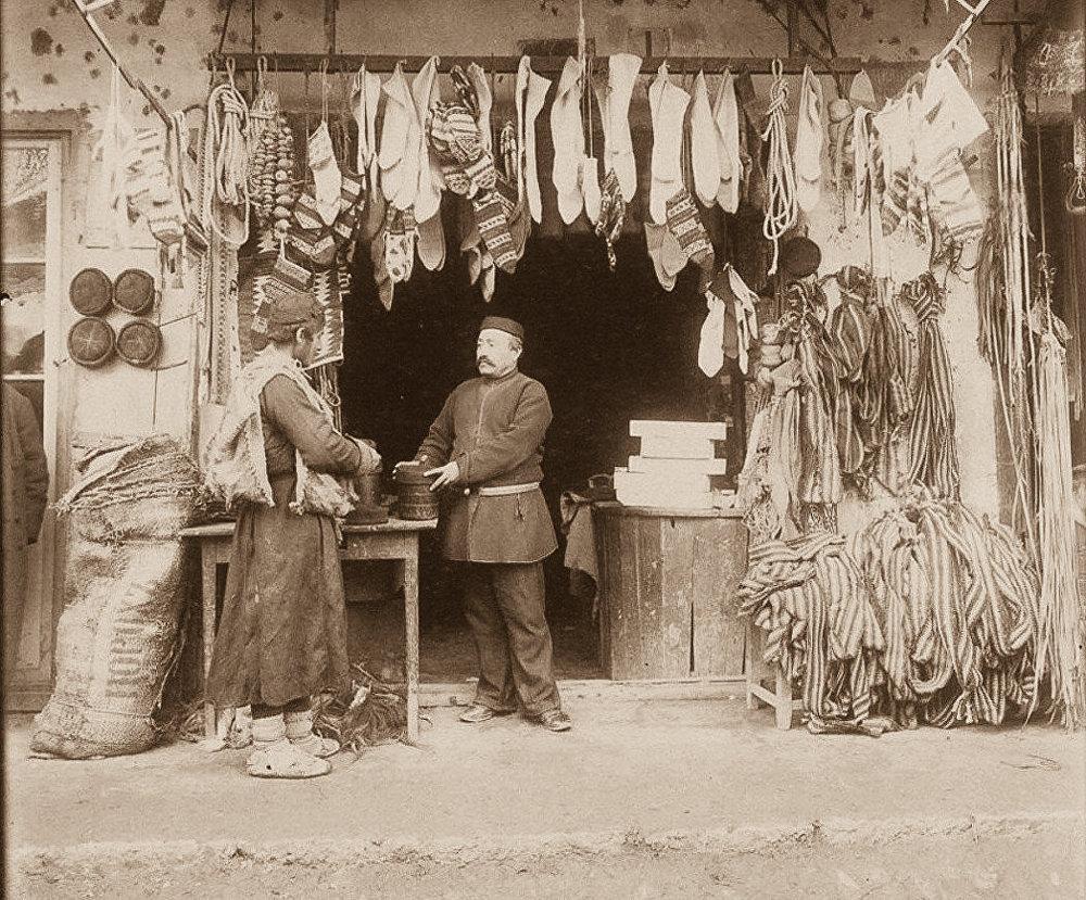 Продавец шерстяных носков и войлочных шапок, и покупатель.