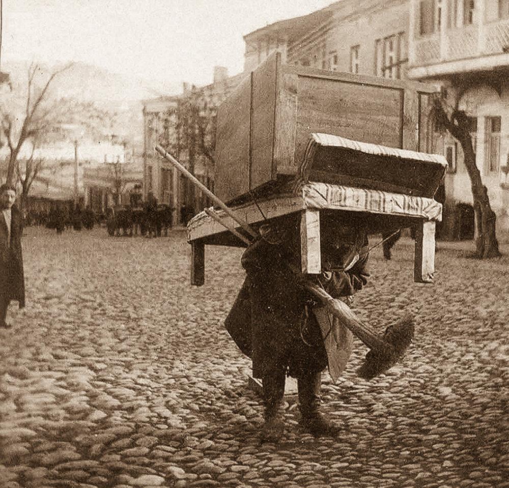 Муша (носильщик) с кушеткой и шкафом на спине
