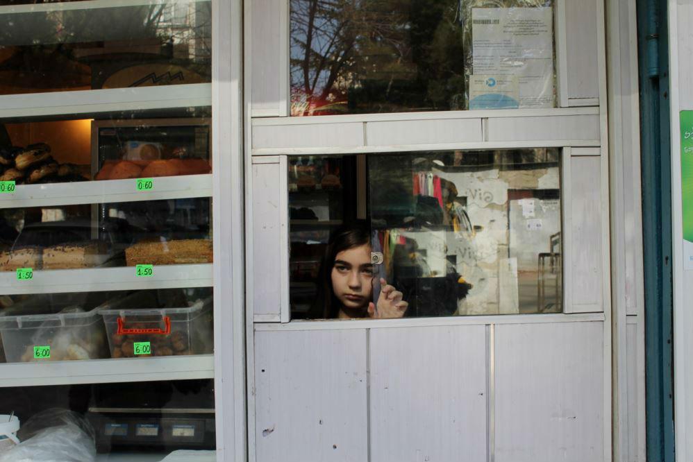 """Школьница помогает родителям в киоске в Тбилиси. Фотограф Гванца Гагнидзе говорит, что """"она только что продала торт мужчине и смотрела, как он уходит"""""""
