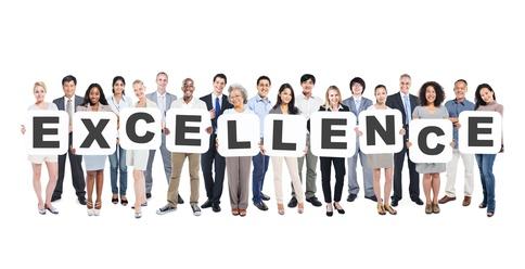 Mitarbeiter halten die Buchstaben Excellence in die Höhe