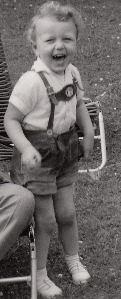 Peter Bach jr. in bayerischer Tracht im Alter von 4 Jahren: Ein kleiner Junge mit kurzen Lederhosen lacht mit Lockenkopf in einem schwarz/weißen Bild zur Kamera. Er steht auf einer Wiese vor einem Liegestuhl.