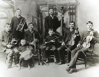 Zur Bach-Genealogie sieht man ein historisches Schwarz-weiß-Foto: Ein Vater und sieben Söhne sind die Bach-Band in den USA. Sechs sitzen, zwei stehen, Jeder hat ein Instrument.