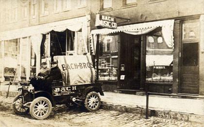 Historische Bach-Genealogie: ein alter Kleinst-LKW auf einem schwarzweißem Foto sthet vor einem Ladengeschäft in den USA. Auf dem vorderen unüberdachten Sitz sitzen 2 Personen. Am Ausleger sieht man den Schriftzug Bach, ebenso auf dem Auto.