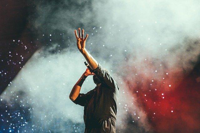 Chanteur en concert, la tête dans les étoiles et le bras dressé, nous cachant sa tête