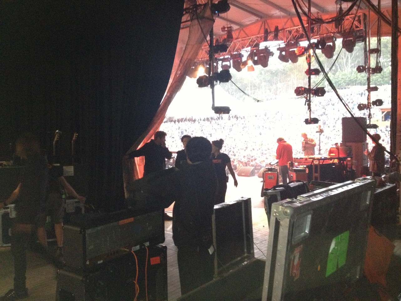 Crew setting up backstage while the previous band is on ...