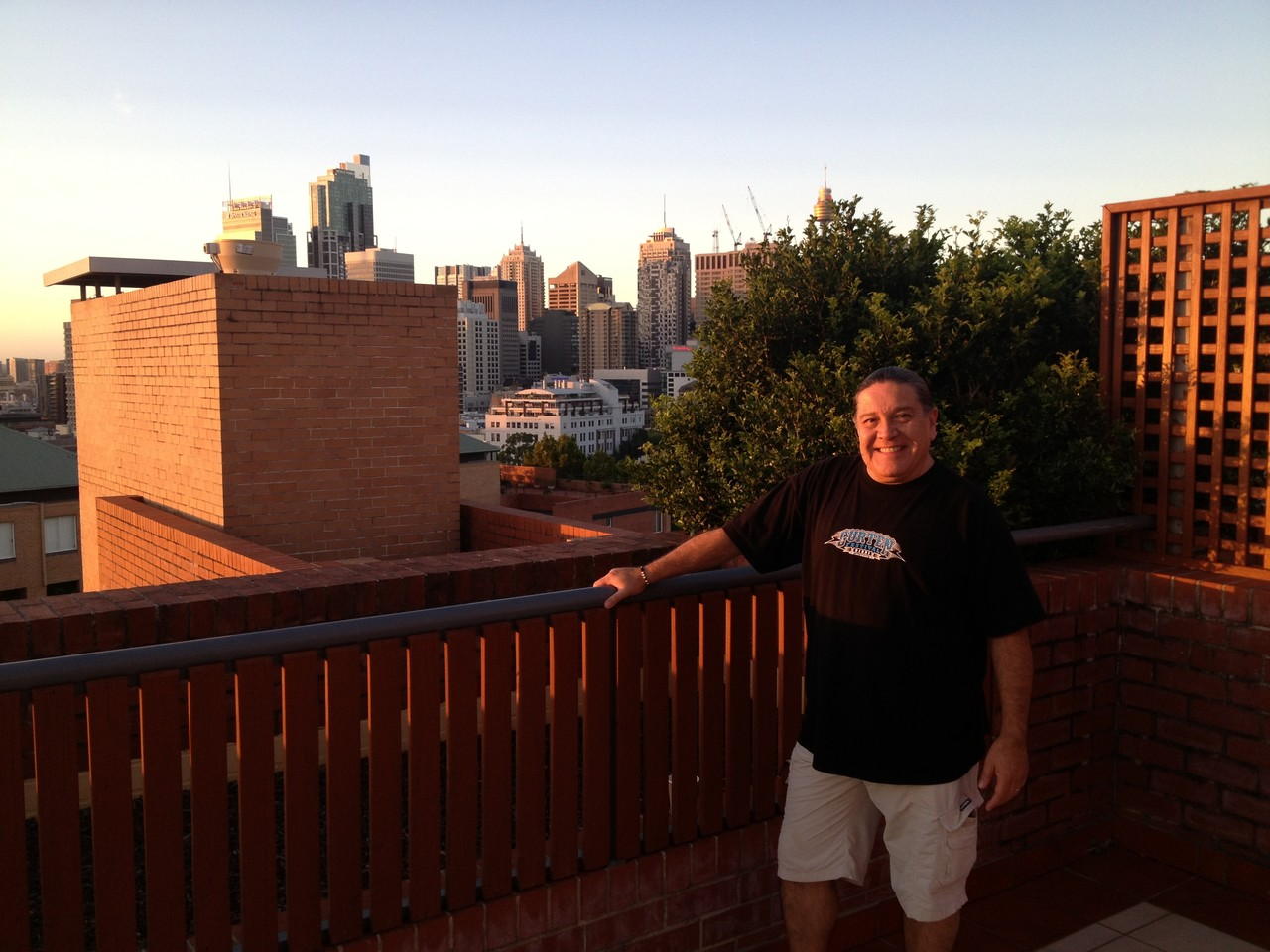 Front of House engineer David Marchant chills out on the balcony as the sun goes down - great view of Sydney. — with David Marchant at Sydney Australia.