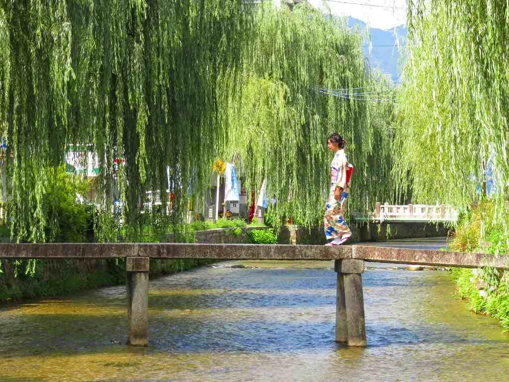 白川に架かる一本橋を渡る着物姿