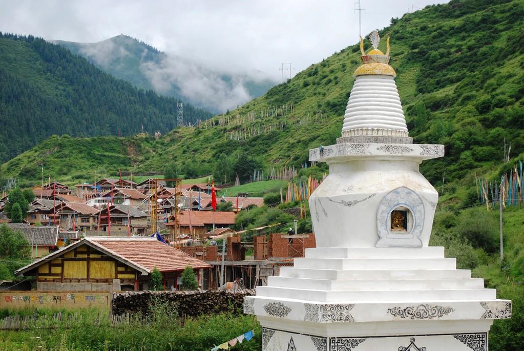 """Village tibétain plutôt modernisé avec au premier plan un """"Chörten"""""""
