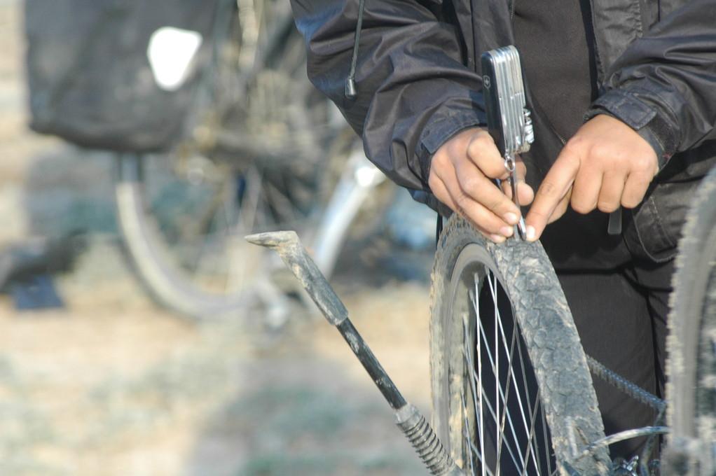 Laeti enlève les cailloux et bris de verre qui s'enfoncent dans les pneux