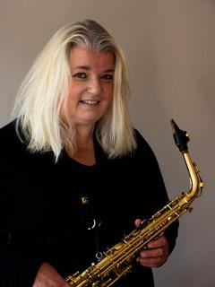 Birgitt Dose hält auf einem schwarz-weiß Foto ein Saxophon in ihrer rechten und eine Querflöte in ihrer linken Hand.