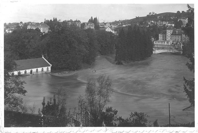27 octobre 1937. Le Gave de Pau déborde en rive gauche, en direction des sanctuaires. A l'arrière-plan, on s'aperçoit que ce dernier passe difficilement sous le pont Saint-Michel qui mène à la basilique. © M.CREPIN
