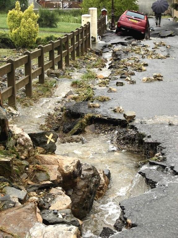 Route ravinée et voiture en mauvaise posture à Bilhères. © Nathalie Magrou