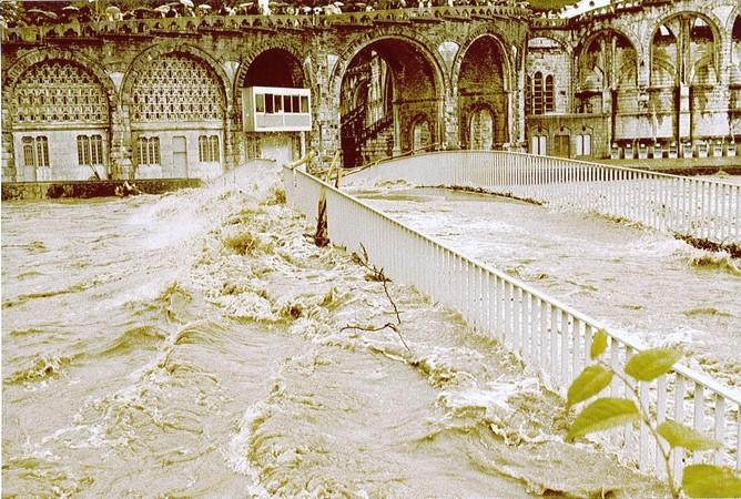 1er Juin 1979. La passerelle de la basilique est submergée par les flots boueux. Un embâcle (accumulation de déchets flottants) s'est formé sur le parapet. Les troncs d'arbres emportés par le courant ont endommagé ce dernier.  © F. DUPLAN