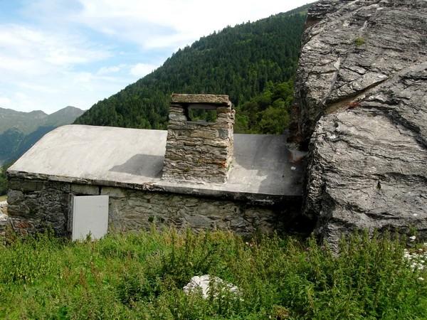 Grange protégée par un immense rocher. L'habitat traditionnel s'est adapté intelligemment au risque d'avalanche. © C-PRIM 2010