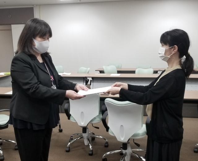 (右)福岡市担当者に要請書を渡す梅本邦子九州原告団代表(九州原告1番母)