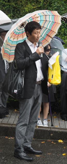 雨の中、応援メッセージを述べる薬害肝炎全国原告団九州支部の小林邦丘さん