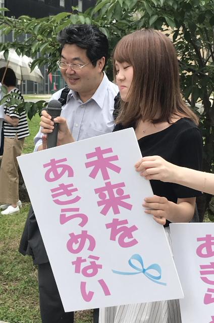 集会で意見陳述に向かう意気込みを語る九州原告15番さん(右)