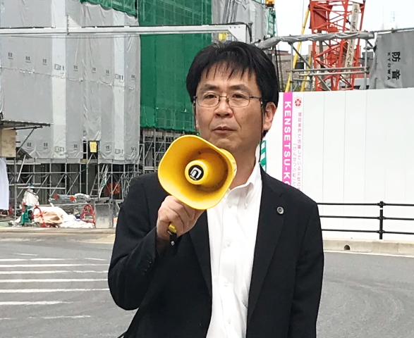 来場者に挨拶する小林洋二九州弁護団代表