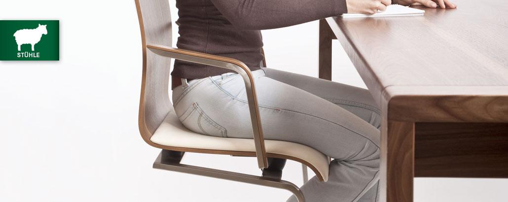 Stühle, ergonomisch und gesund sitzen – Frau sitzt an einem Tisch