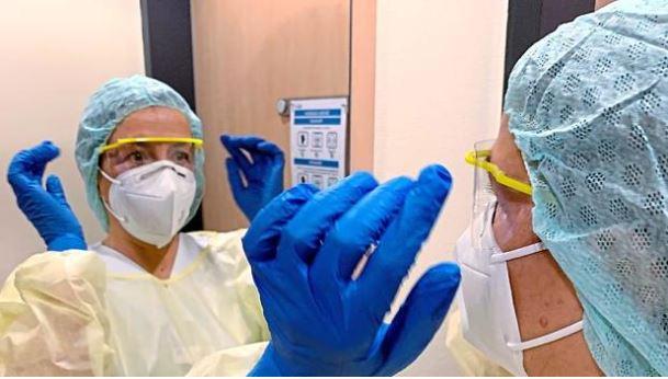 Krankenschwester Doris Gartner zieht sich in der Schleuse die Schutzkleidung an. In der Infektionsabteilung des Klinikums, wo sie arbeitet, gehört das schon immer zum Prozedere. Neu hinzugekommen ist mit Corona die Schutzbrille. Foto: Klinikum Ingolstadt
