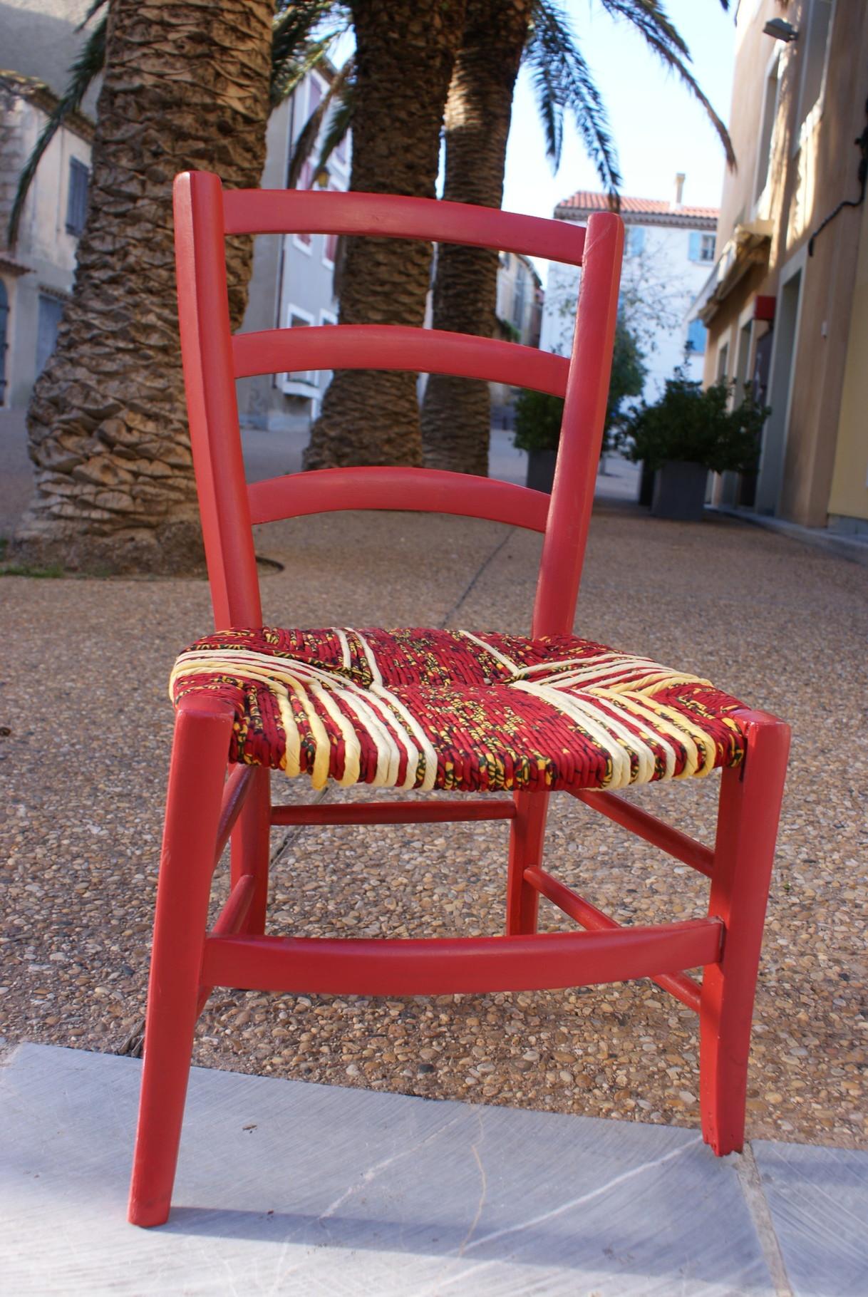 Ancienne chaise basse, repeinte dans un rouge vif. Paillage en torons de tissus (anciens draps teints en jaune et tissu africain Wax dans les tons rouges). Vue 1