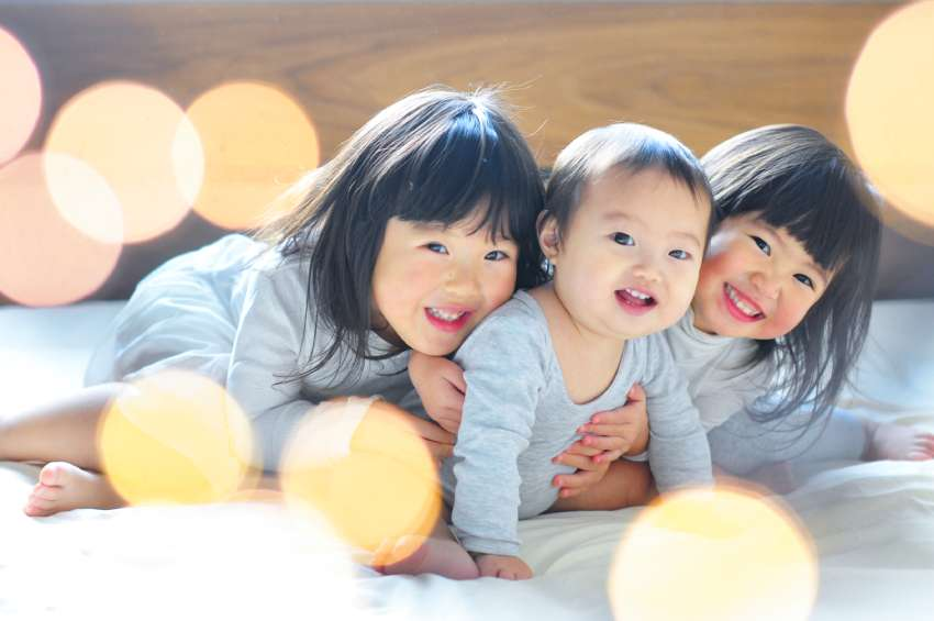 2人のお姉ちゃんが赤ちゃんに抱きつき、3人とも笑顔でこちらを見ている写真です。