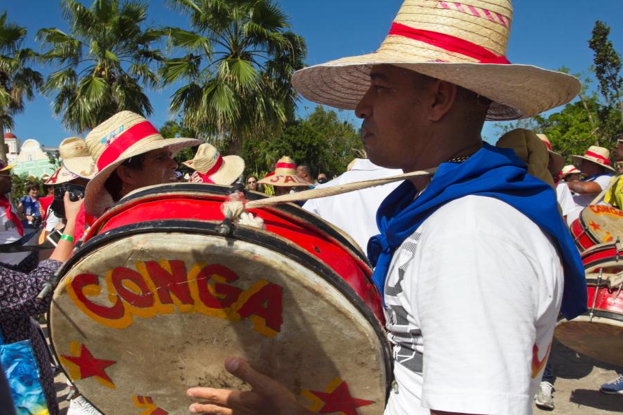 Kubietis gatvėje su dideliu būgnu ir skrybėle