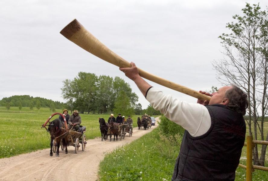 Marijus Čekavičius sutinka žirgus ir vežimuose sėdinčius žygeivius pūsdamas žemaitišką gaudytę
