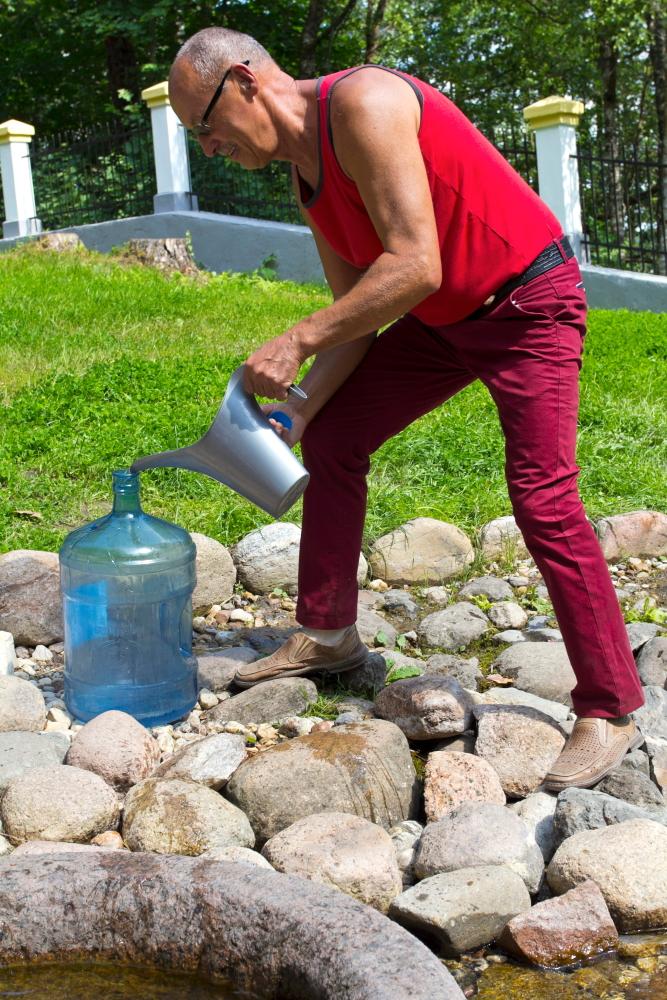 Iš Krokulės šaltinio prie Šventosios upės Utenos rajone vyras semia vandenį