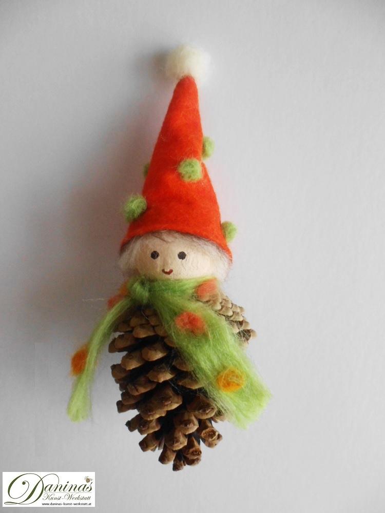 Wichtel Waldfried. Handgefertigte Figur aus Kiefernzapfen, mit grün-orangem Schal aus Wolle und oranger Filz Mütze mit grün-weißen Bommeln.