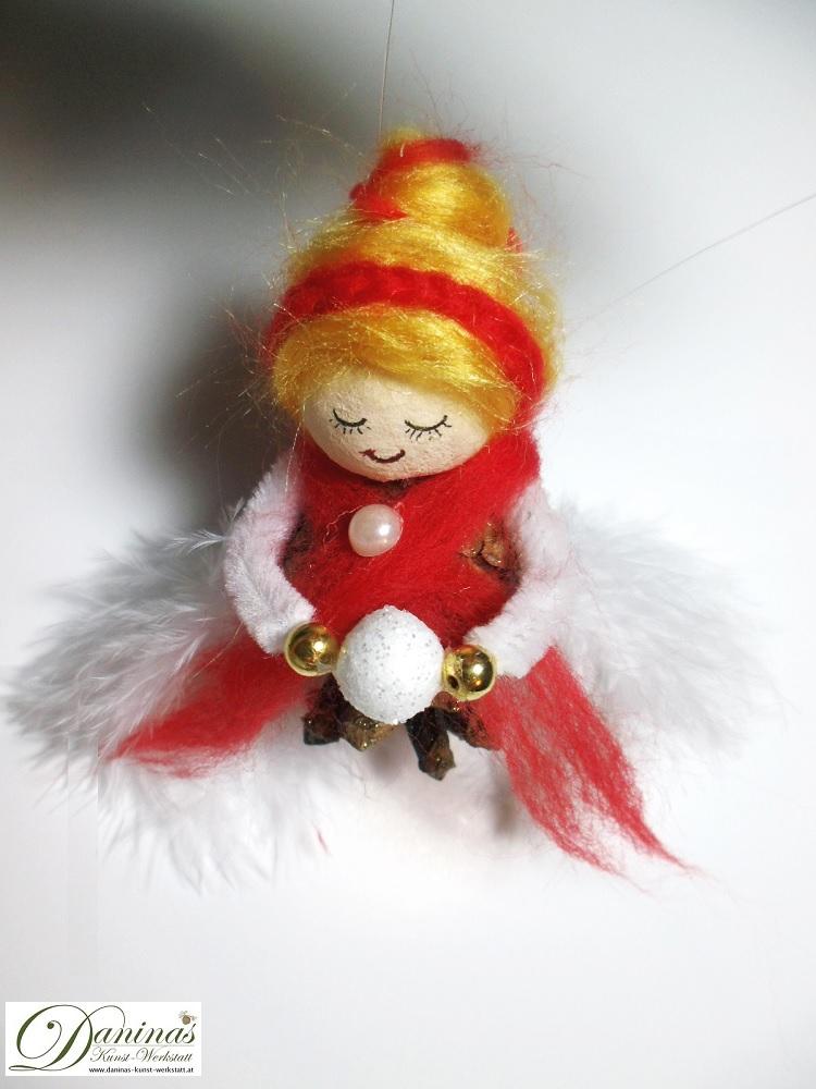 Winterfee Schneeflocke, Seitenansicht. Handgefertigte Figur aus Kiefernzapfen, mit goldenen Haaren und rotem Schal aus Wolle, weißen Federnflügeln und einem Schneeball.