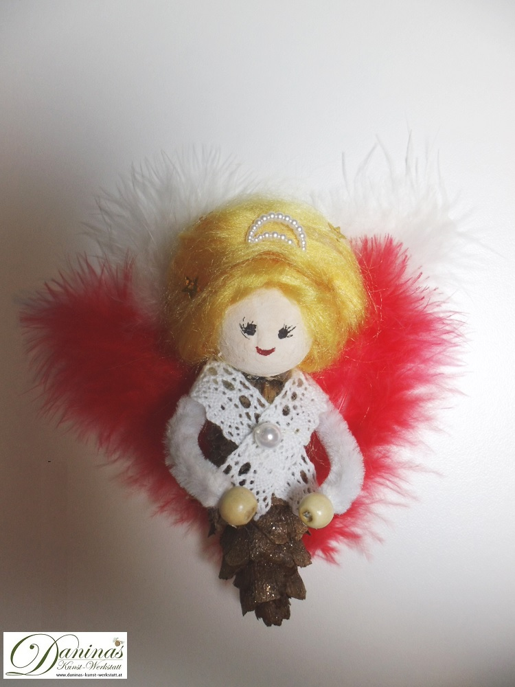 Engel Morgenröte. Handgefertige Figur aus Douglasienzapfen, mit blonden Haaren aus Wolle, einer Schmuckperlenkrone, roten Federnflügeln und einem Spitzenjäckchen