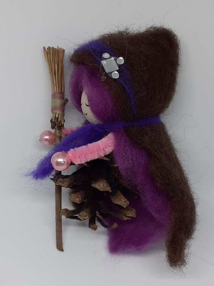 Hexe Viola Seitenansicht. Handgefertigte Figur aus Kiefernzapfen, mit violetten langen Haaren und nadelgefilztem braunen Hexenmantel aus Wolle, silberne Ziersteinen, Hexenbesen aus Kiefernnadeln