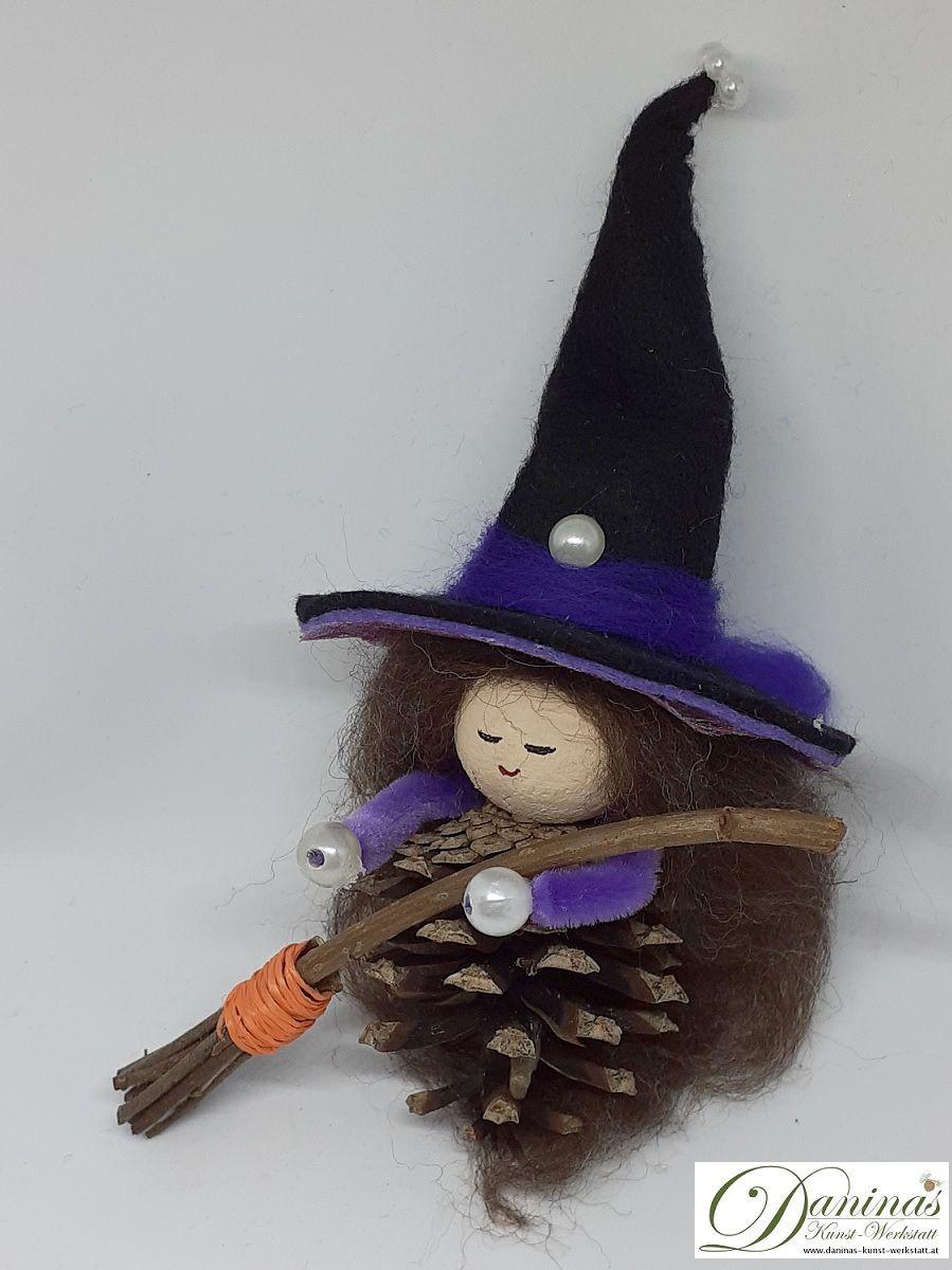 Hexe Lupinia. Handgefertigte Märchenfigur aus Kiefernzapfen, mit braunen langen Haaren aus Wolle, schwarz-violettem Hexenhut aus Filz und Hexenbesen aus Zweigen