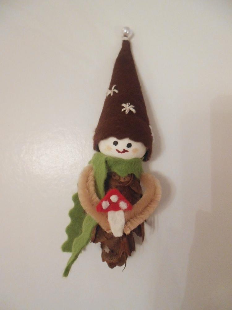 Glückswichtel Benjamin Pilz. Handgemachte Figur aus Douglasienzapfen, mit grünem Schal, brauner bestickter Zipfelmütze und einem Fliegenpilz aus Filz.