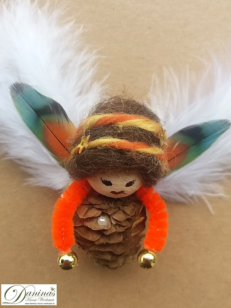 Schutzengel Peachy. Handgefertige Figur aus Lärchenzapfen mit braunen Haaren und buntem Haarband aus Wolle sowie bunten und weißen Federnflügeln.