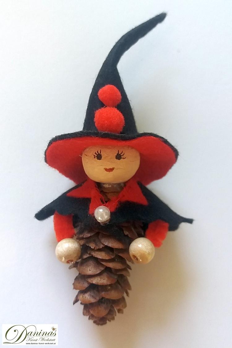 Hexe Wallburga. Handgefertigte Märchenfigur aus Douglasienzapfen, mit einem schwarz-roten Filz Jäckchen und einem Hexenhut mit roten Bommeln